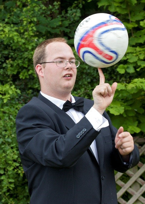a man in a suit spining a ball on the end of his finger